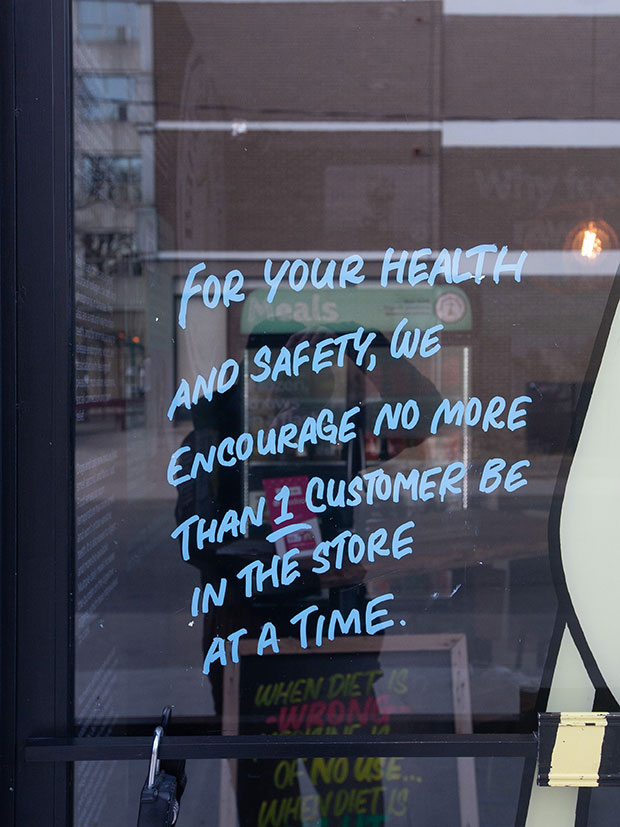 A sign reads 'for your health and safety, we encourage no more than 1 customer be in the store at a time.
