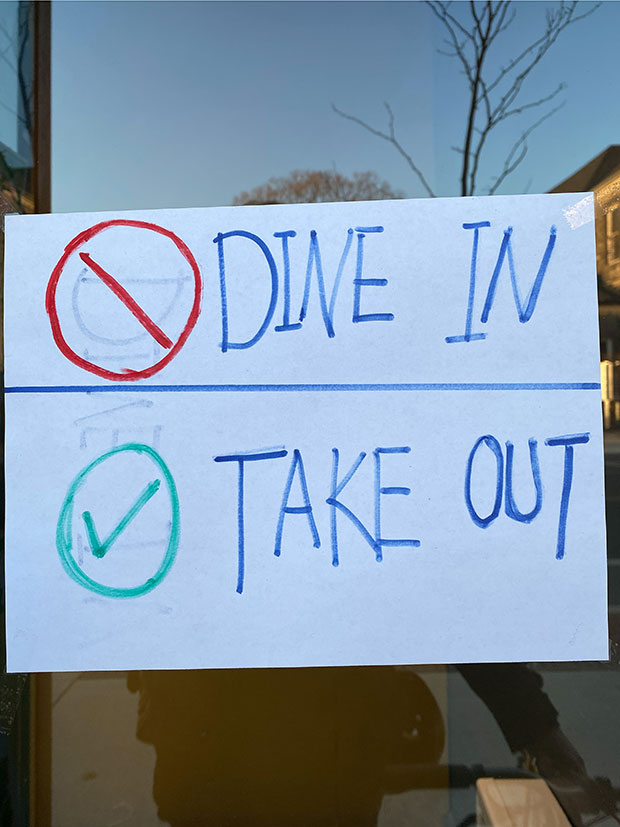 A sign shows a red interdiction sign next to the words 'dine in' and a green checkmark next to the words 'take out.'
