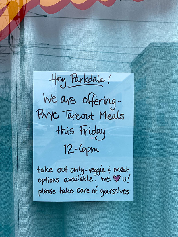 A sign reads 'Hey Parkdale! We are offering PWYC takeout meals this Friday 12 - 6 p.m.