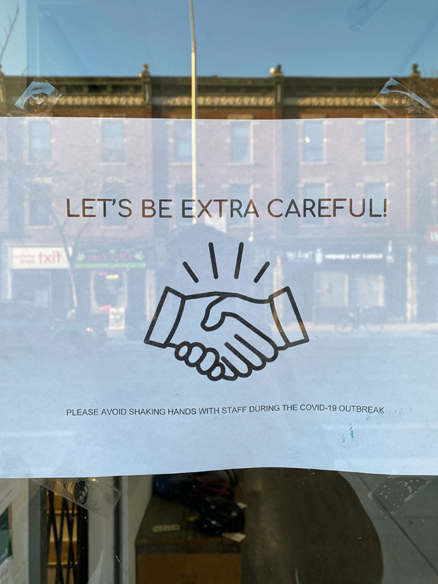 A sign reads 'let's be extra careful' and shows two hands shaking.