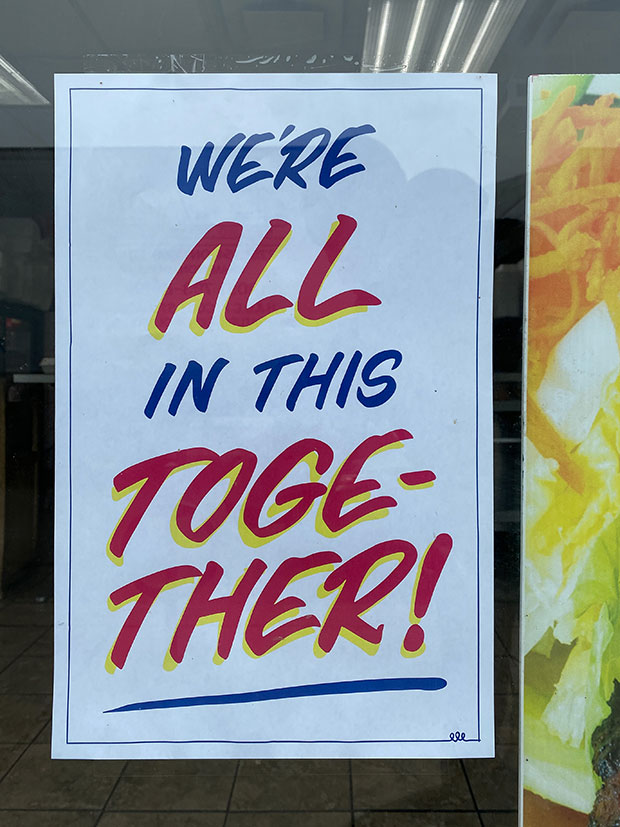A sign reads 'we're all in this together.'