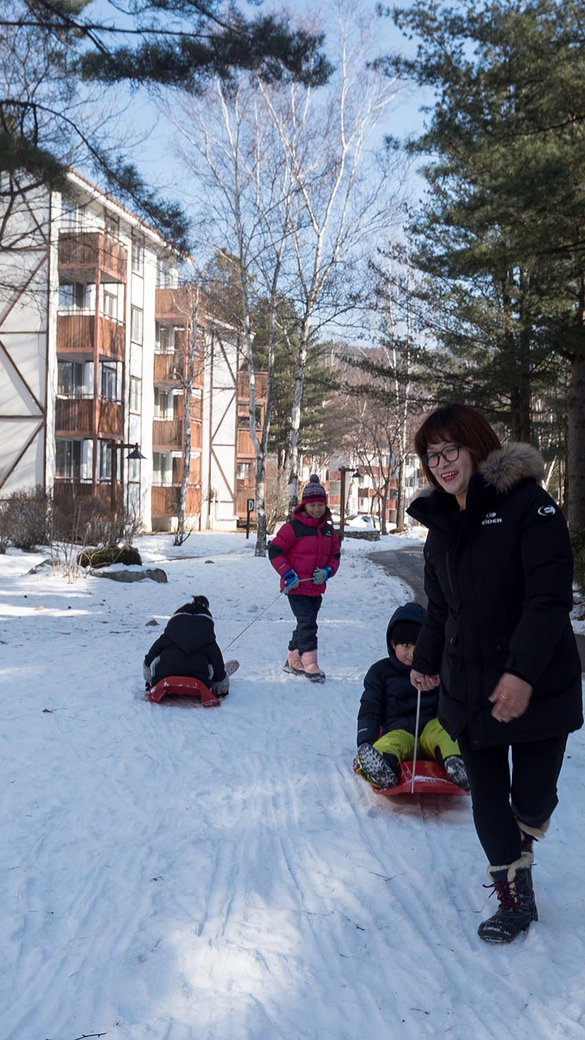 A family plays with a sled while visiting Yongpyong Ski Resort.