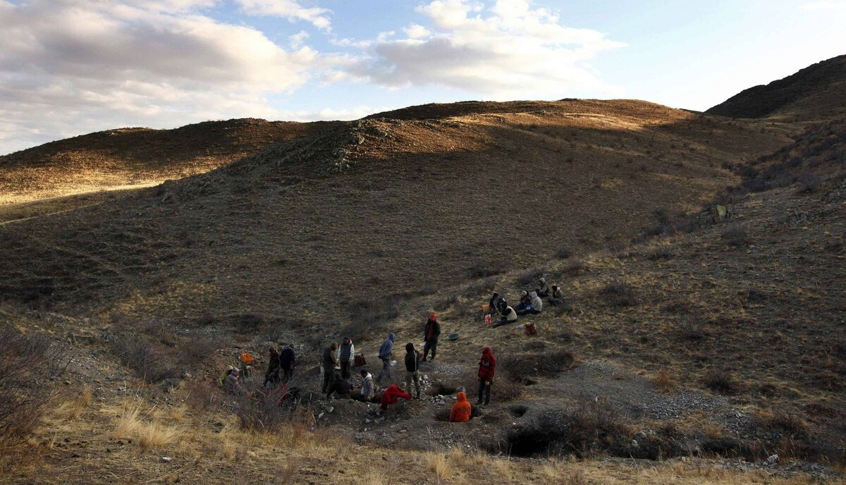 Small-scale miners dig holes as they search for gold on a small hill overlooking grasslands located around 200 km south-west of the Mongolian capital city Ulan Bator.