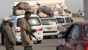 Two Libyan rebels check vehicles crossing toward Egypt at the Egyptian-Libyan border crossing near the border town of Musaed, Libya, on March 16, 2011.