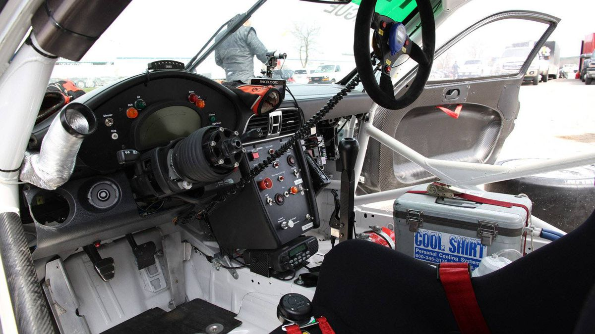 The interior of a GT3 Cup car is stripped of all upholstery to save weight and allow quick access to mechanical and electrical systems. A removable steering wheel makes it easier for drivers to climb in and out. The ice chest on the right is connected to cooling lines that run through the drivers's suit.