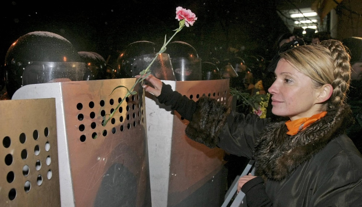 Opposition leader Viktor Yushchenko's top ally Yulia Timoshenko places carnations into shields as riot police guard the Ukrainian presidential administration building in Kiev, Tuesday, Nov. 23, 2004. Several thousand opposition leader Viktor Yushchenko supporters marched to the presidential administration building, skirting some heavy trucks that blocked the street and standing in front of riot police who guarded the building. Yushchenko declared himself the winner of a disputed presidential election and took a symbolic oath of office Tuesday as tens of thousands of his supporters stood their ground in the tense, freezing streets of Kiev for a third straight day. (AP Photo/POOL,Anatoly Medzyk)