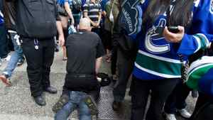 Security arrest a spectator while Vancouver Canucks fans prepare to watch first period Stanley Cup final game 5 action against the Boston Bruins in downtown Vancouver, Friday, June 10, 2011.