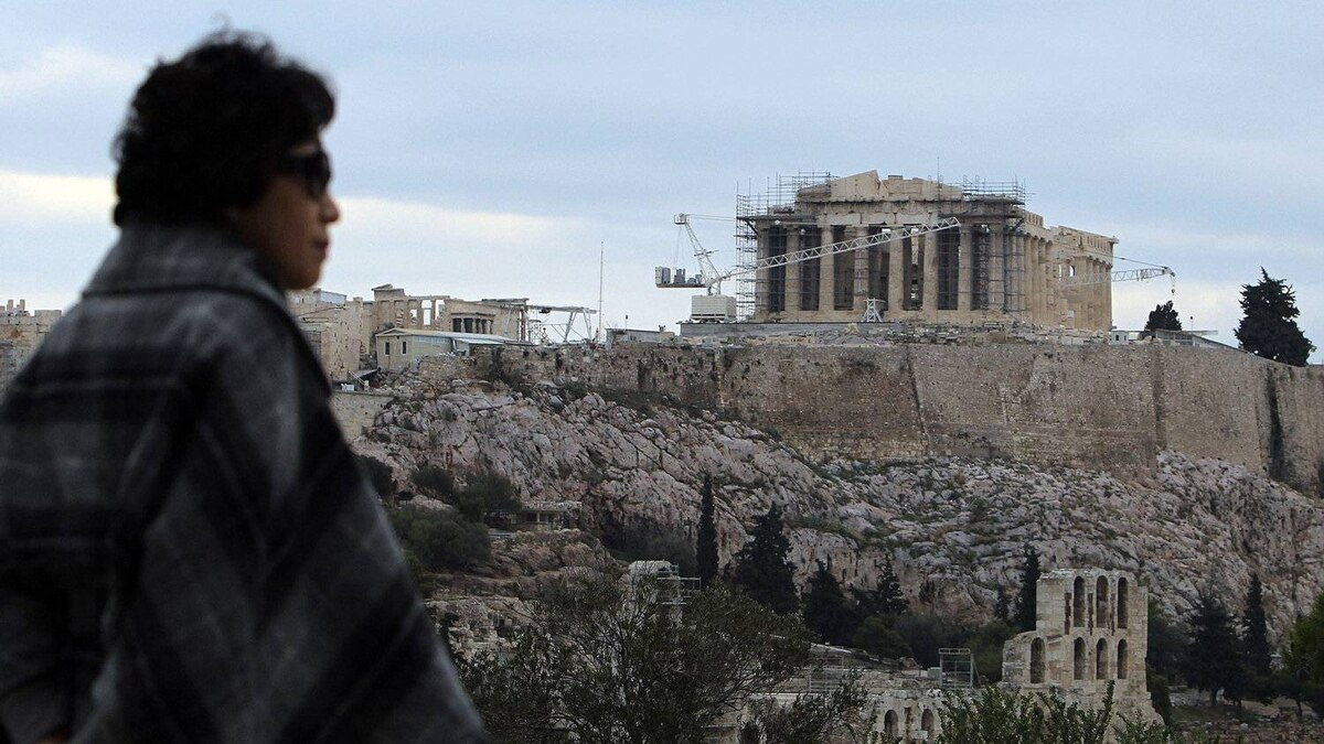 A tourist stands on the Pnyx hill with the Acropolis hill in the background during a strike in Athens, Saturday, Dec. 24, 2011. Greek guards say scores of archaeological sites and museums across the country will be shut down over weekends beginning at Christmas as they strike to protest the lack of extra weekend pay.