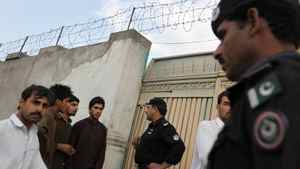 Guards and local visitors stand by the entrance to the former home of Osama bin Laden near Abbottabad, Pakistan.