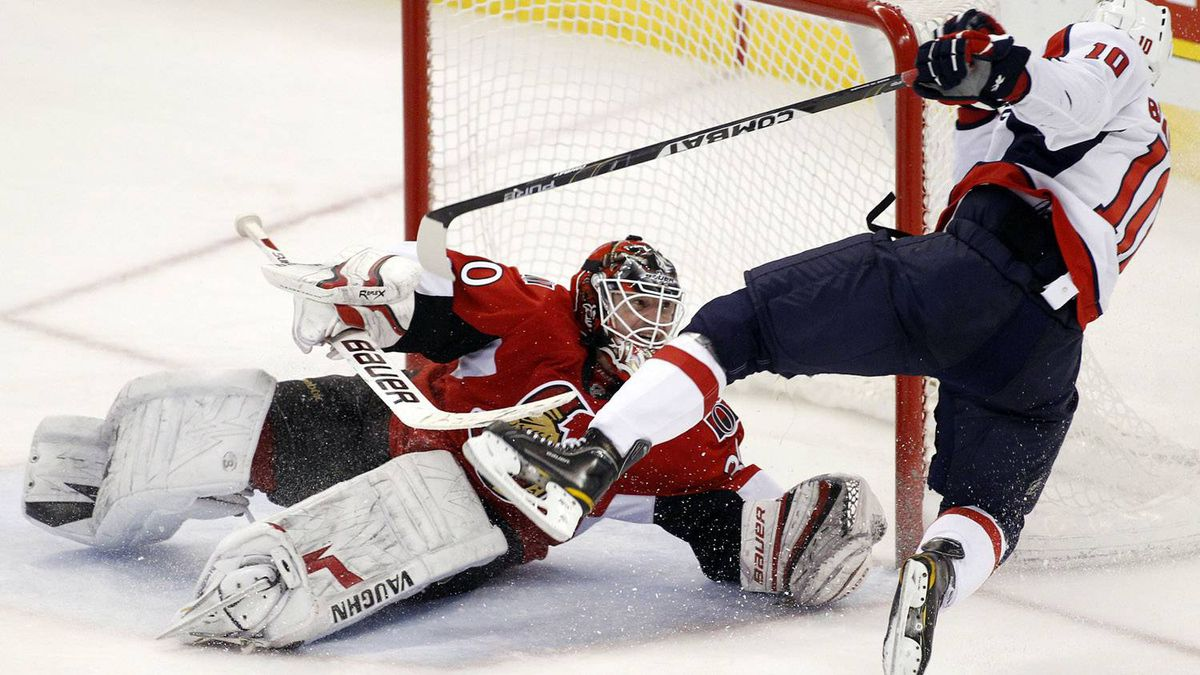 Washington Capitals' Matt Bradley trips over Ottawa Senators' goalie Brian Elliott during the third period of their NHL hockey game in Ottawa December 19, 2010. The Caps won 3-2. REUTERS/Blair Gable