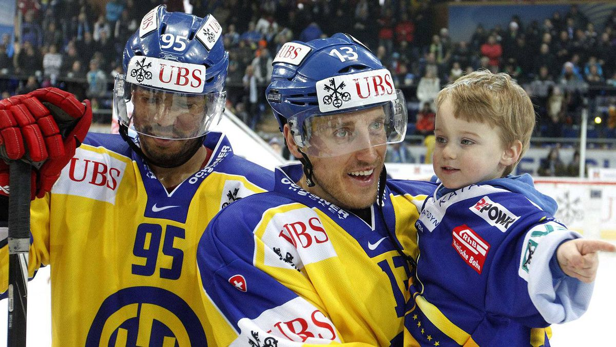 HC Davos' Robbie Earl (R) stand beside as his team mate Peter Sejna holding his son Ownen after winning their final game against Dinamo Riga at the Spengler Cup ice hockey tournament in the Swiss mountain resort of Davos December 31, 2011. REUTERS/Arnd Wiegmann
