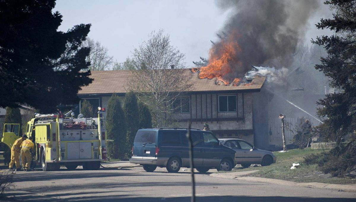 Firefighters work to save a house in Slave Lake.