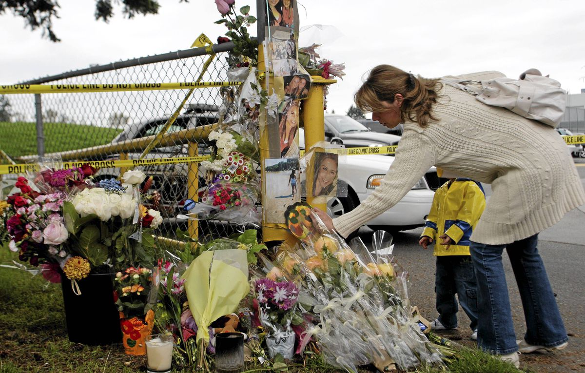 A mother and son place a memento at the memorial of slain teen Laura Szendrei on Oct. 8, 2010, in Delta, B.C.