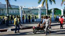 Men carry an injured woman in front of the presidential palace after the Port-au-Prince earthquake.