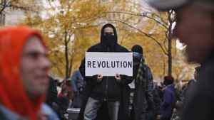 A protester affiliated with the Occupy Wall Street movement holds up a sign while attending a daily meeting at Zuccotti Park in New York Nov.19, 2011.