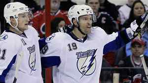 Tampa Bay Lightning's Steven Stamkos (91) and Dominic Moore (19) celebrate Moore's goal against the Carolina Hurricanes during the second period of an NHL hockey game in Raleigh, N.C., Saturday, March 26, 2011. Hurricanes' Patrick Dwyer (39) skates off at right. The Bolts won 4-2. (AP Photo/Gerry Broome)
