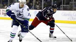 Vancouver Canucks' Henrik Sedin (33) takes the puck past Columbus Blue Jackets' Jared Boll (40) during the first period of their NHL hockey game in Columbus, Ohio December 23, 2010.