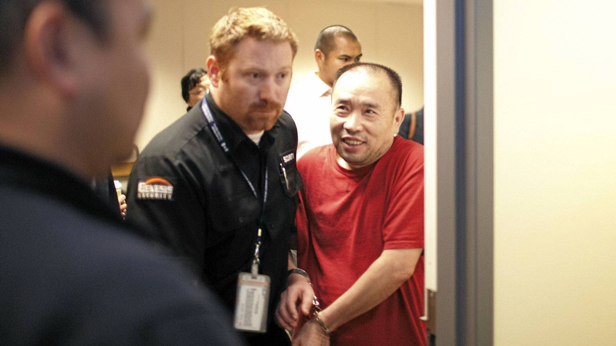 Lai Changxing is escorted out after an Immigration and Refugee Board detention hearing in Vancouver on Tuesday, July 19, 2011.
