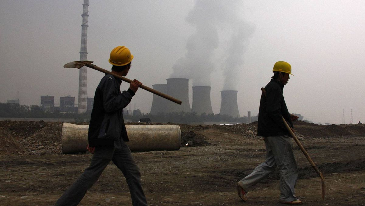 A coal-burning power station can be seen behind migrant workers as they walk carrying their shovels on the construction site of a water canal, being built in a dried-up river bed located on the outskirts of Beijing.