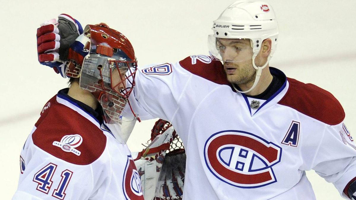 Montreal Canadiens goalie Jaroslav Halak (41), of Slovakia, and Andrei Markov, top right, of Russia, celebrate a 2-1 win as Washington Capitals left wing Alex Ovechkin (8), also of Russia, skates away in Game 5 of the NHL hockey playoffs, Friday, April 23, 2010, in Washington. (AP Photo/Nick Wass)