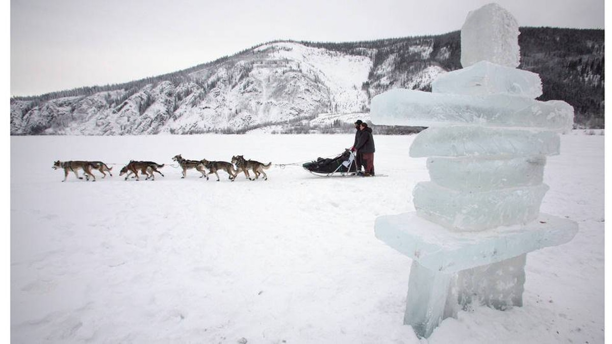 This Feb. 15, 2008, file photo shows Dan Kaduce and his wife Jodie Bailey of Chatanika, Alaska, riding the runners of Kaduce's dogsled together as they pass an ice Inukshuk on the Yukon River on their way to the Dawson City, campground after checking in at the halfway point during the annual 'Yukon Quest' International Sled Dog Race.