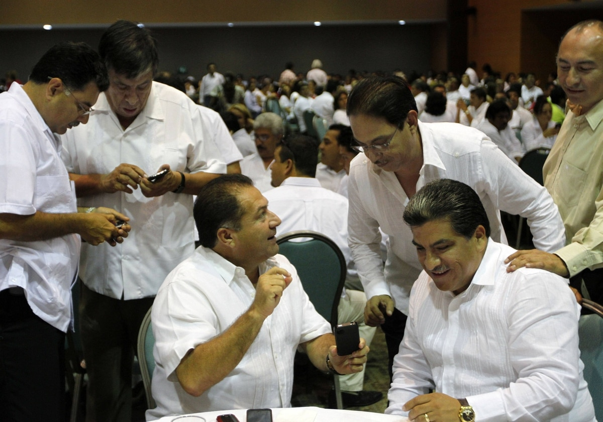 A group of Enrique Pena Nieto's supporters examine the photos they took of the Mexican presidential candidate during a campaign meeting in Ciudad del Carmen, in Campeche, Mexico on May 16, 2012.