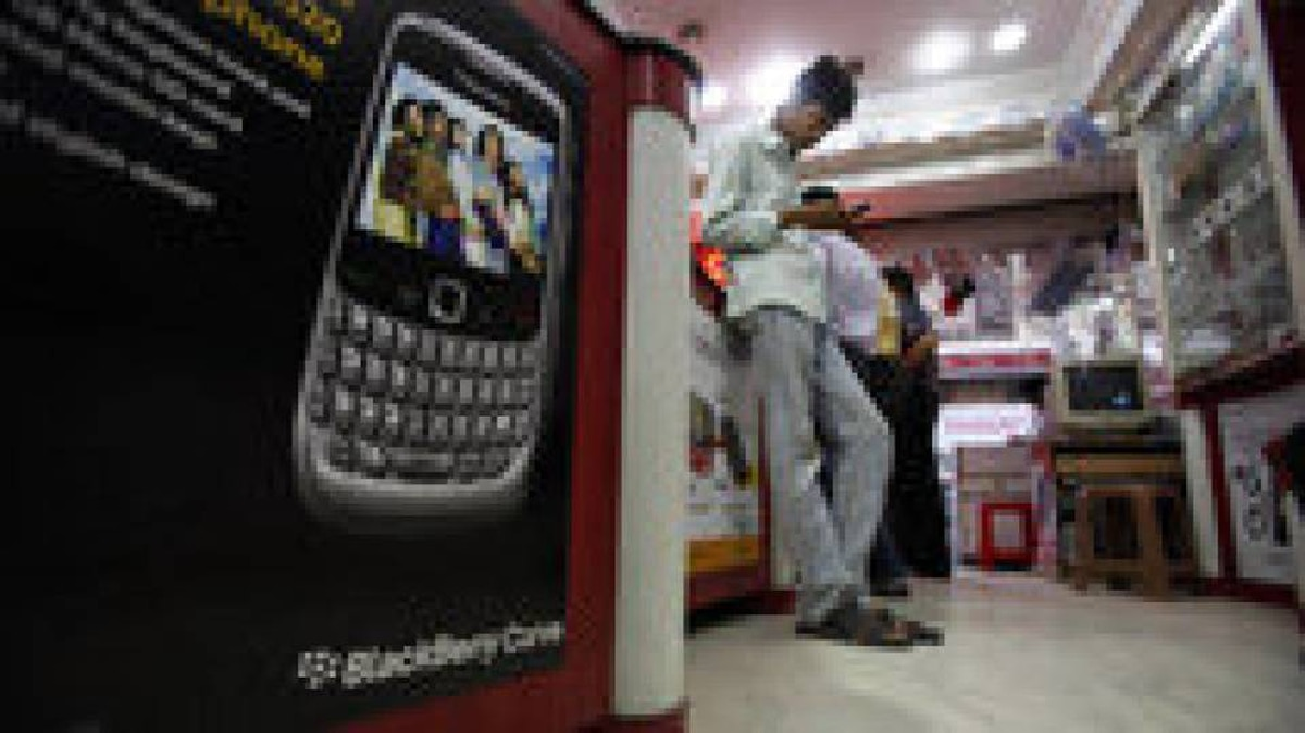 An Indian man checks his handset at a shop in Hyderabad, India, Friday, Aug. 13, 2010.