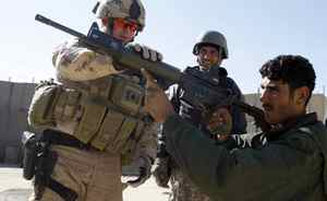 In this Jan. 17, 2010 file photo, Canadian Police Constable Craig Dickie, left, from Milton, Ontario, part of the Canadian Police Contingent, demonstrates a gun to an Afghan Police officer at a checkpoint in Kandahar City.