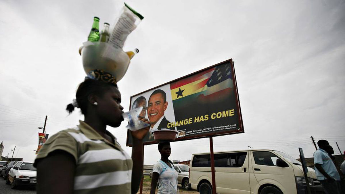 A woman carries goods on her head past a billboard depicting the likenesses of Ghana's President John Atta Mills and U.S. President Barack Obama in the Ghanaian town of Cape Coast July 9, 2009.