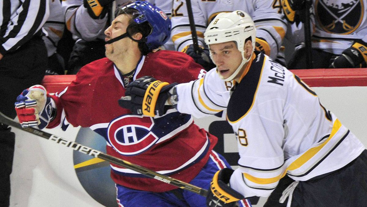 Montreal Canadiens' Aaron Palushaj takes a hit from Buffalo Sabres' Cody McCormick during second period NHL hockey action Monday, November 14, 2011 in Montreal.