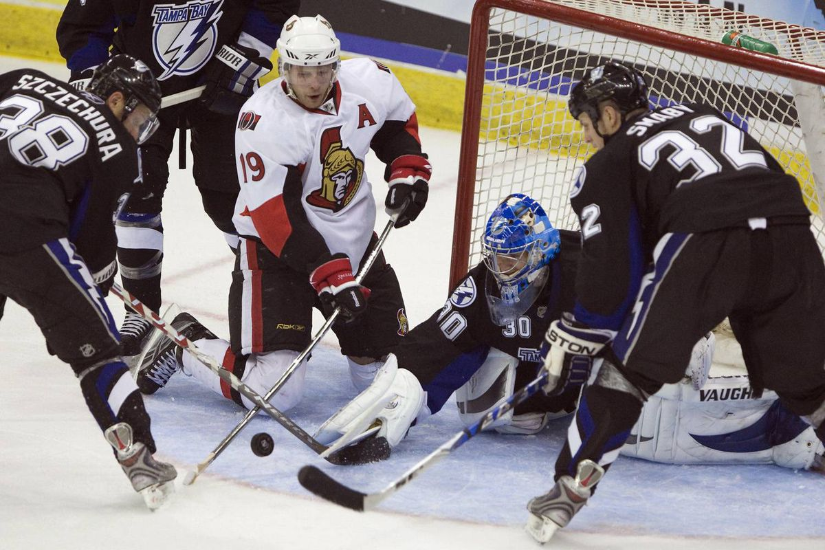Ottawa Senators' Jason Spezza, centre, tries to knock in the loose puck in front of Tampa Bay Lighting's goalie Antero Niittymaki at the Brandt Centre in Regina, Sask., Monday, Sept. 21, 2009.