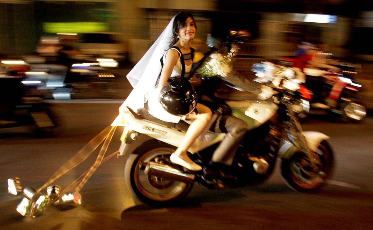 "A couple dressed in wedding outfits ride their motorcycle during a ""Halloween Convoy of Terror"" in Cali October 29, 2009. Every year motorcycle enthusiasts dress up in their scariest outfits and ride around Cali to celebrate Halloween."