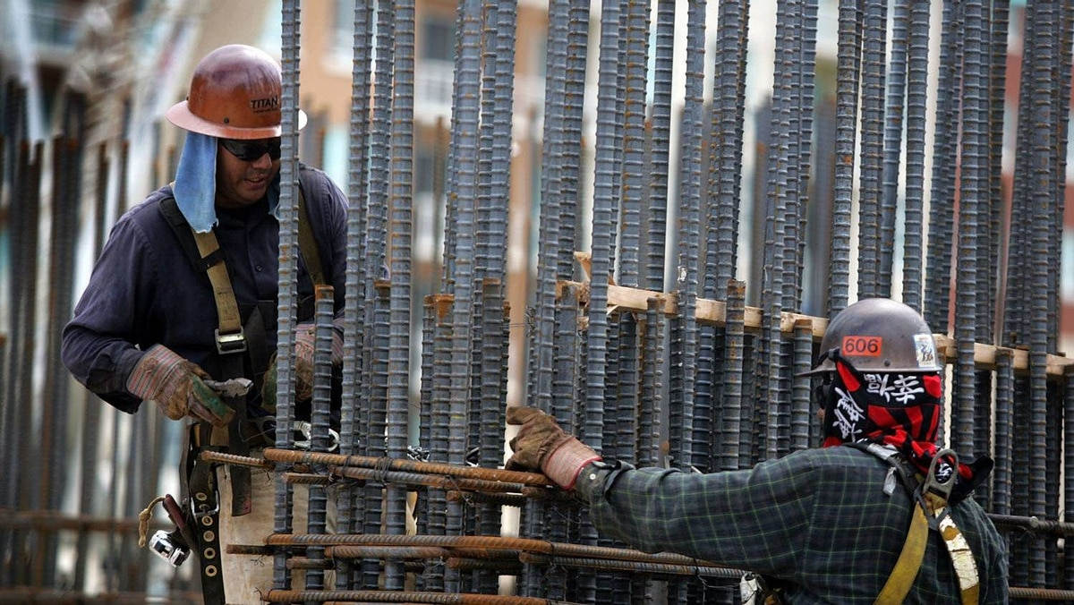 File photo of construction workers attaching rebar to a building project in Miami, Fla.