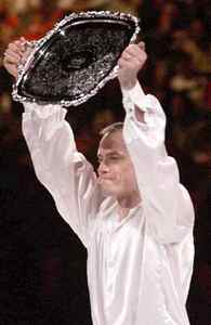 Four-time world champion Kurt Browning holds up the silver platter he received after winning the men's World Professional Figure Skating Championships at the MCI Center in Washington, Saturday, Dec. 13, 1997. Browning has won three consecutive times.