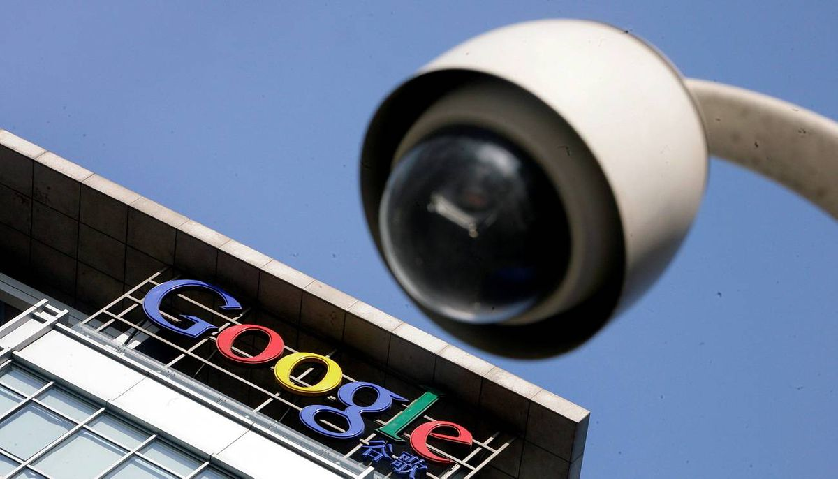 The Google logo is seen on the top of its China headquarters building behind a road surveillance camera in Beijing.