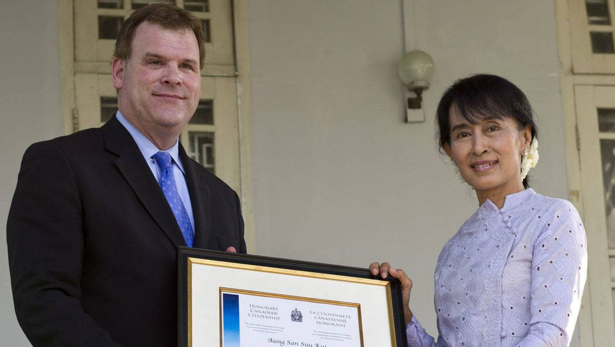 Nobel laureate Aung San Suu Kyi receives her honorary Canadian citizenship from the hands of Foreign Affairs Minister John Baird at her home in Yangon, Myanmar Thursday, March 8, 2012.