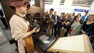 A stand attendant in traditional garb demonstrates the use of a Gutenberg printing press at the 63rd Frankfurt Book Fair October 14, 2011.