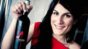 Sarah Liberatore, founder of STLTO, holds up a bottle of her red wine