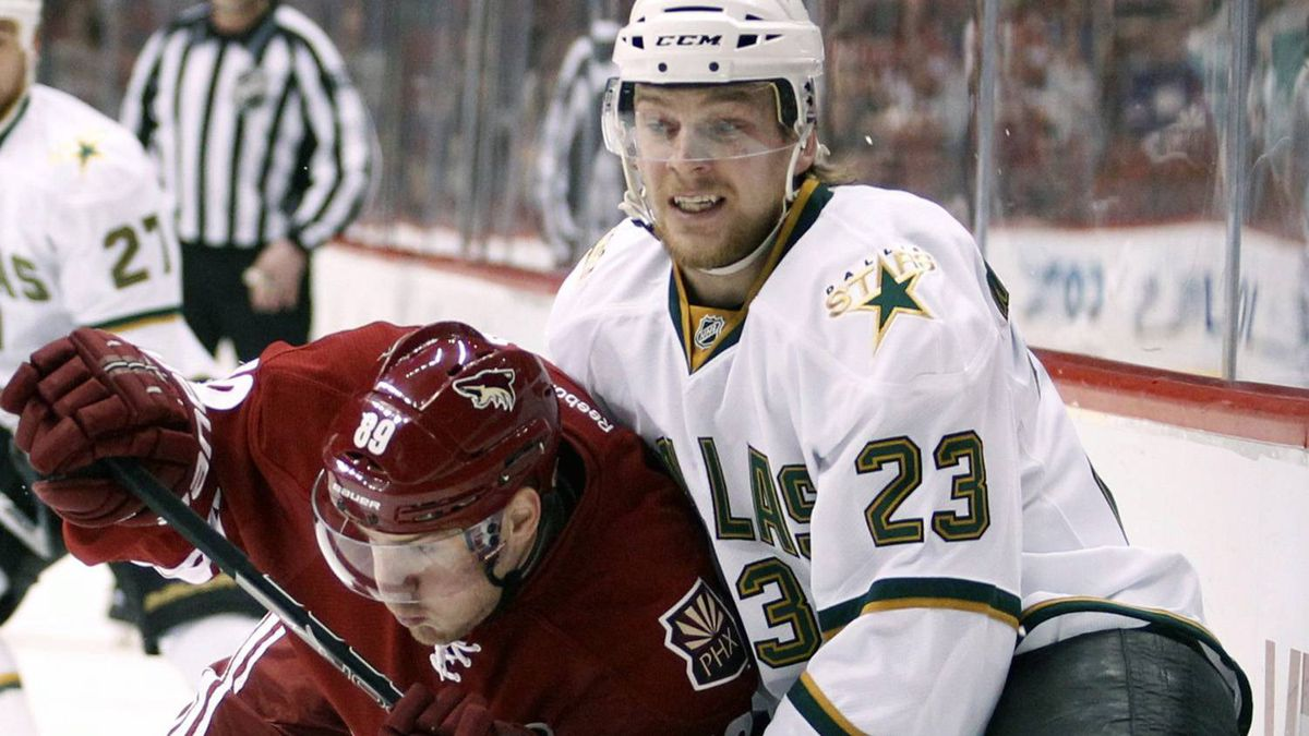 Phoenix Coyotes right-winger Mikkel Boedker, left, of Denmark, checks Dallas Stars centre Tom Wandell, right, into the boards in the first period of an NHL hockey game on Saturday, Feb. 18, 2012, in Glendale, Ariz. The Coyotes won 2-1 in OT. (AP Photo/Paul Connors)