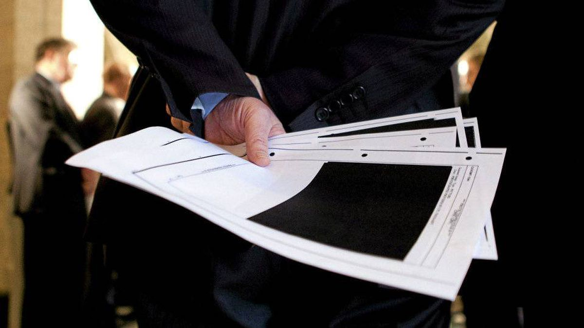 Liberal MP Bob Rae holds blacked-out detainee-related pages released by the government.
