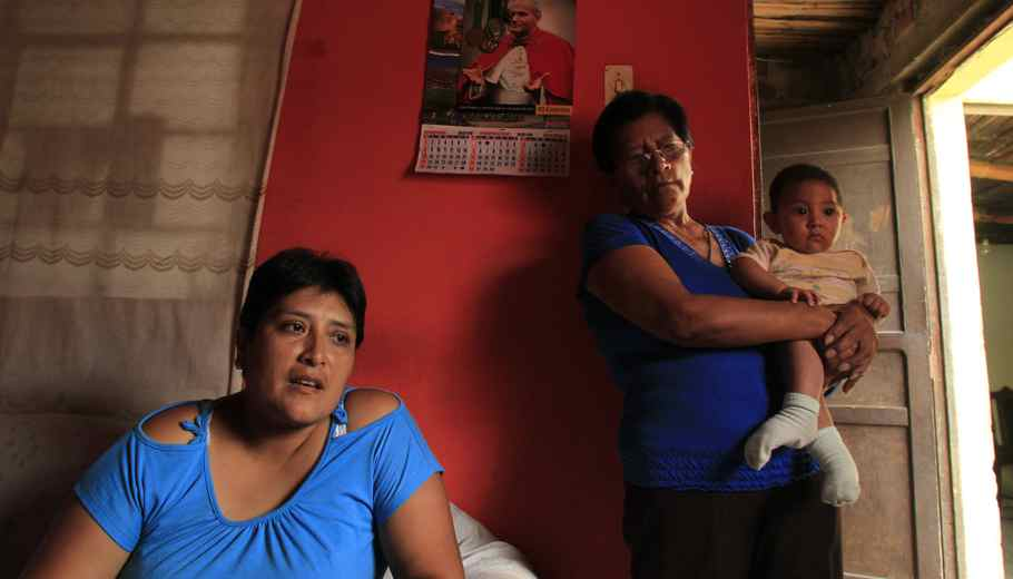 Giovanna Figueroa de Alba (L), whose husband, Javier Alba, was injured in in the crash, is next to her mother Maria Esther Yaya who is carrying Giovanna's 6-months-old baby Ashraf Alba at their home in Comas.