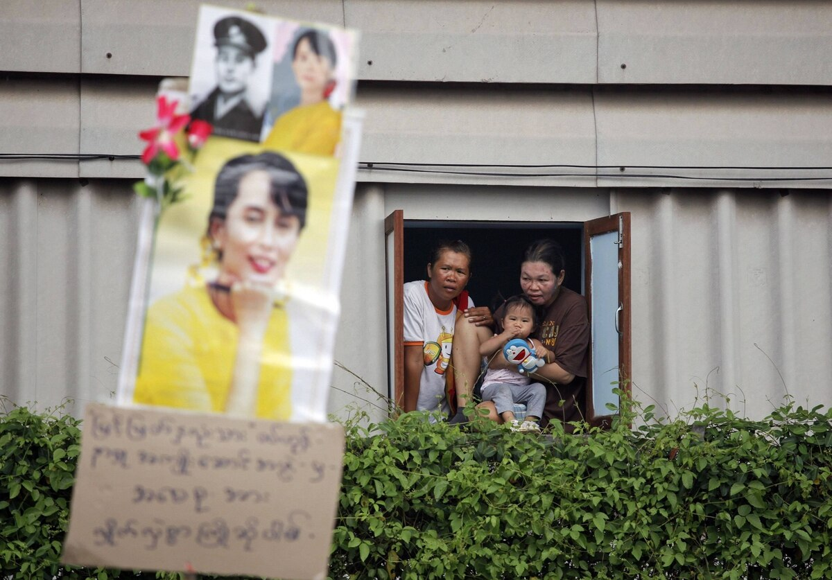 People look through the window as Nobel Peace Prize winner Aung San Suu Kyi arrives at the Nationality Verification Centre for migrant workers from Myanmar, in Samut Sakhon province, Thailand.