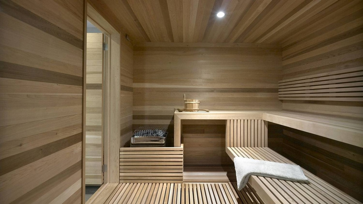 The house's most elaborate architectural showpiece is the basement spa. There is a careful geometry in the cedar benches, their linear patterns arranged to intersect and flip from floor to wall to ceiling without a jagged edge.