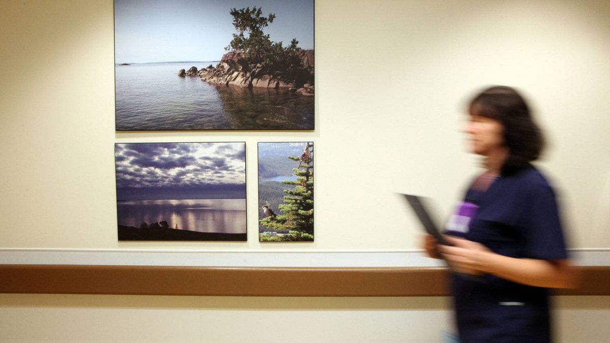 A nurse at the Royal Jubilee Hospital walks by art work, earth tone colours and new elderly friendly hand railings inside the Patient Care Centre in Victoria, B.C.