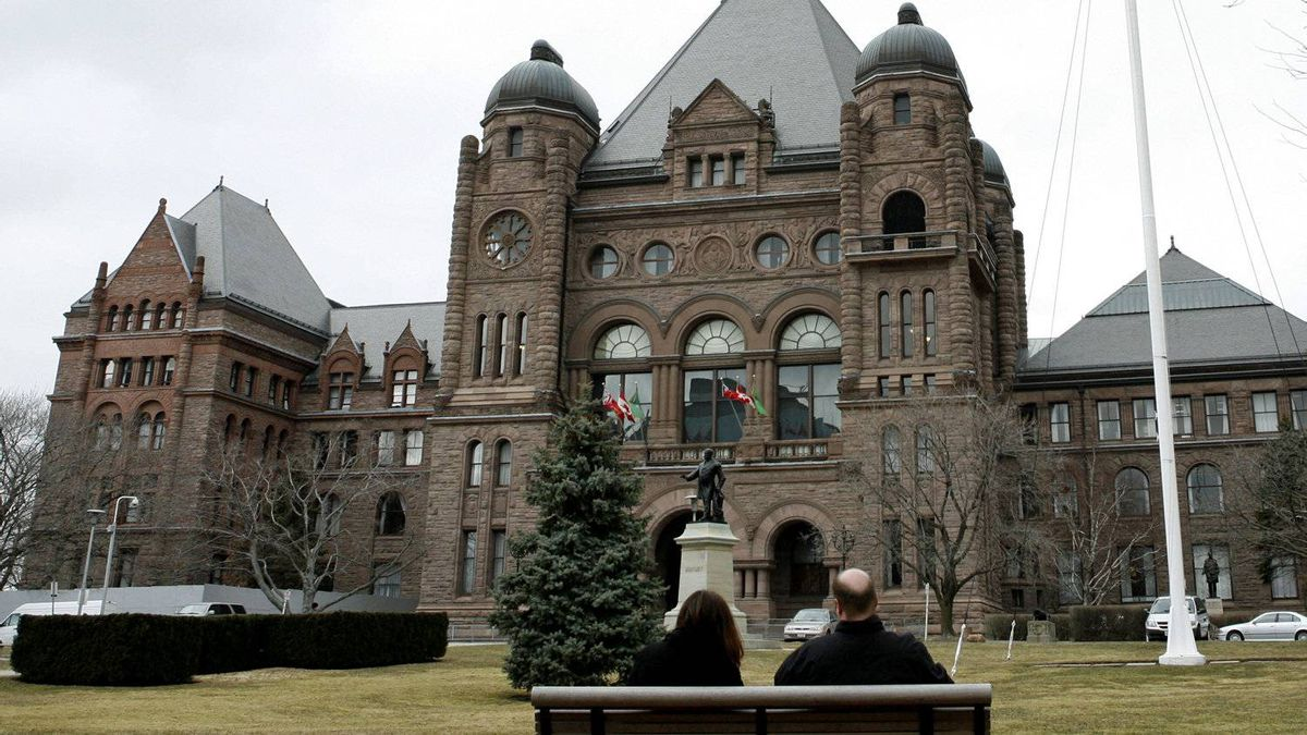 Toronto residents take a break on a bench outside the Ontario Legislature at Queen's Park in 2009.