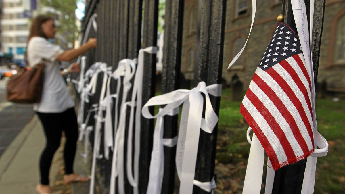 "woman ties a ""Ribbon of Remembrance"" onto the fence at St. Paul's Chapel on September 8, 2011 in New York City."