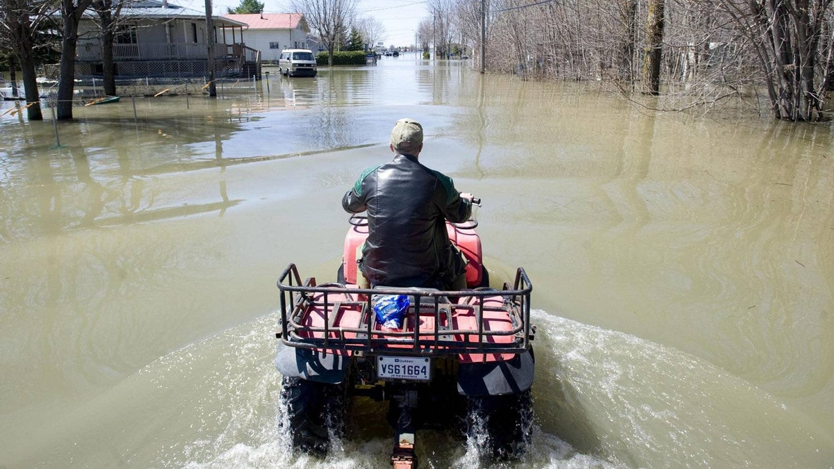 Reginald Bouchard makes his way along a street immersed in flood waters in the town of Ste-Anne-de-Sabrevois, Que., south of Montreal, Saturday, April 30, 2011.