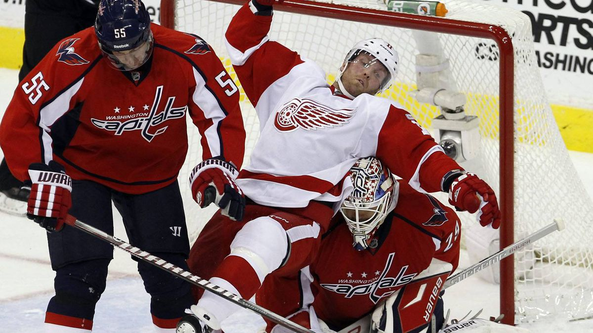 Detroit Red Wings right wing Daniel Cleary, center, trips over Washington Capitals goalie Tomas Vokoun, right, of the Czech Republic after colliding with Capitals defenseman Jeff Schulz (55) during the second period of an NHL hockey game in Washington, Saturday, Oct. 22, 2011. The Capitals beat the Red Wings 7-1. (AP Photo/Ann Heisenfelt)