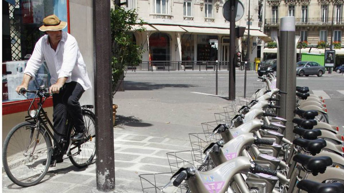A man rides his bicycle past a row of Velib bicycles in Paris, Saturday July 14, 2007.