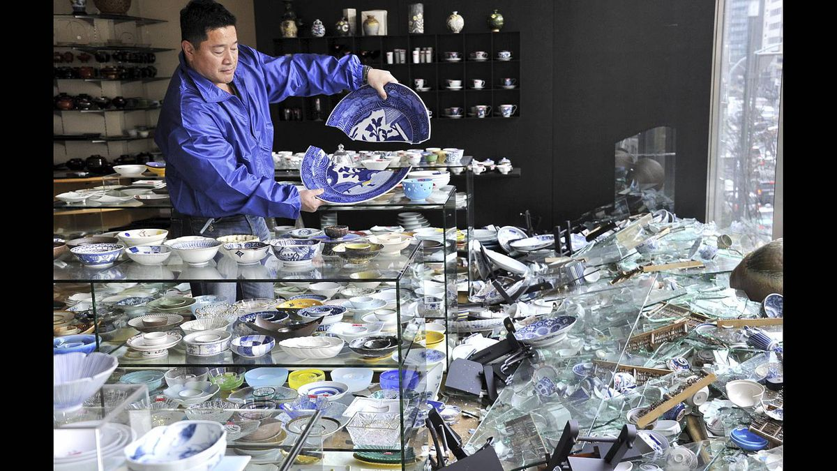 The owner of a ceramic shop checks his damaged wares following the massive 8.9-magnitude earthquake in Tokyo on March 11, 2011.